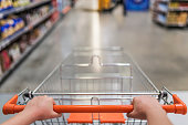 Female hand and shopping trolleys while browsing an aisle at supermarket