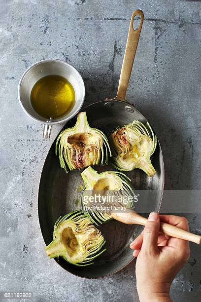 Female hand brushing fresh artichoke with olive oil.Top view