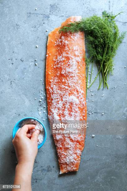 Female hand covering salmon fillet with sea salt.Preparing cured salmon.