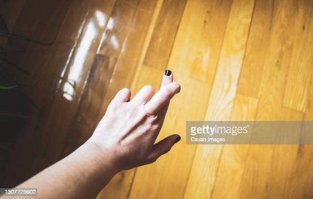 female hand crossing fingers against parquet floor - black nail polish stock pictures, royalty-free photos & images