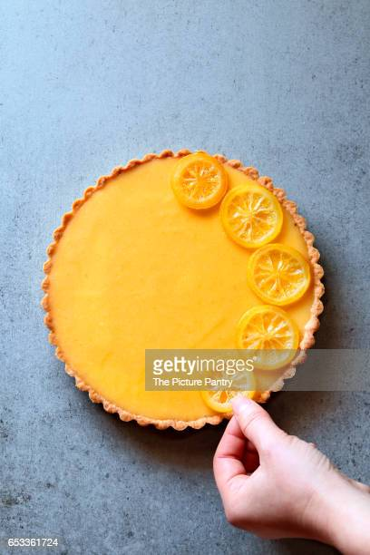 Female hand decorating a lemon tart with lemon slices.Top view