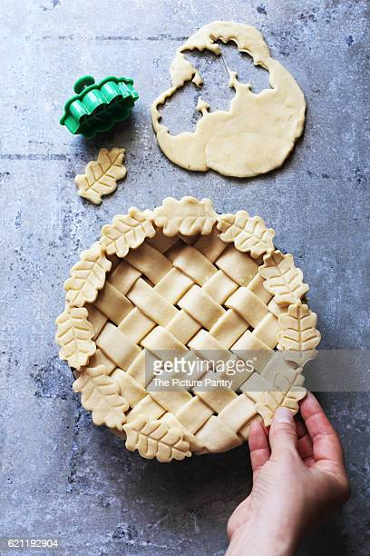 Female hand decorating a pie with leaves .Top view.