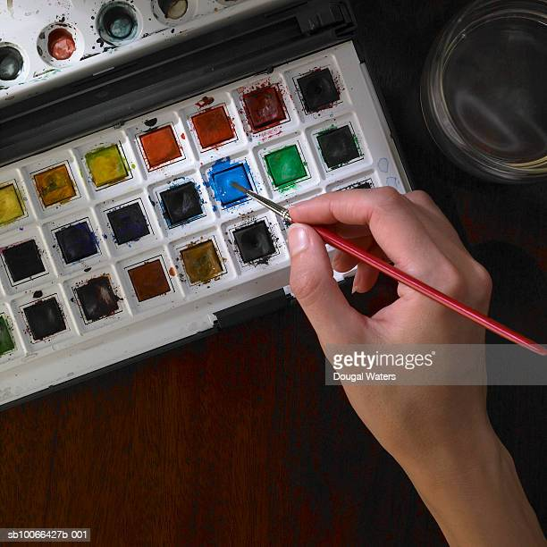 Female hand dipping paint brush into water colour pallet