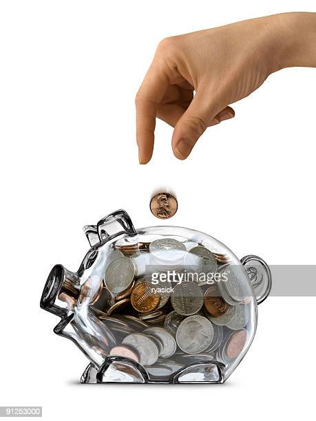 Female Hand Dropping Coin Into Full Clear Piggy Bank Isolated