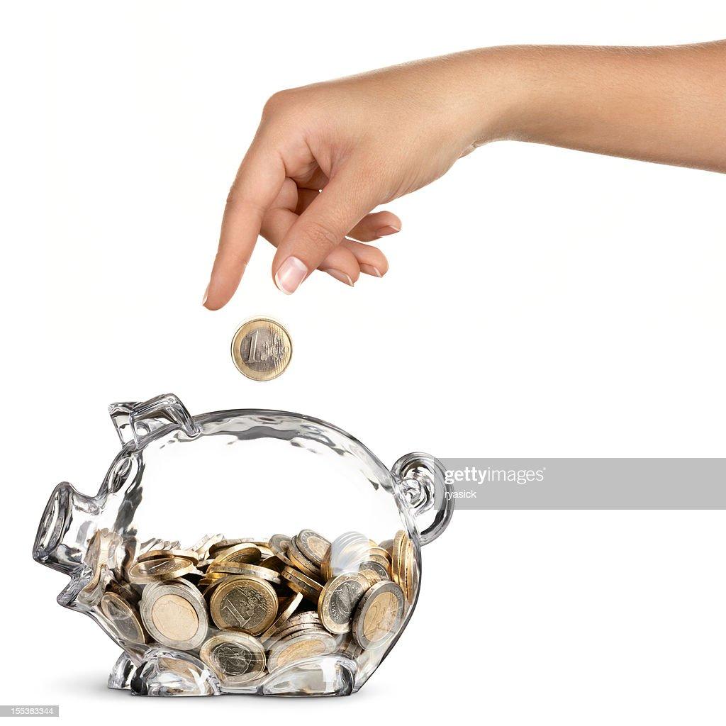 Mano de mujer caída Euro alcancía completa y media máscara : Foto de stock
