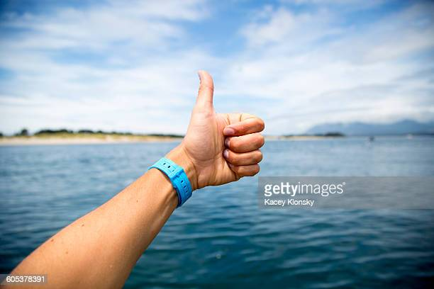 Female hand giving thumbs up over Nehalem Bay, Oregon, USA