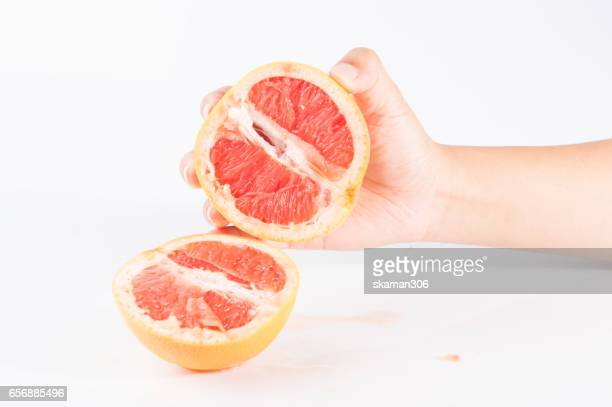 female hand hold grapefruit cutting half