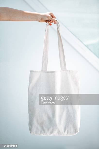 female hand holding a organig tote bag mock up - トートバッグ ストックフォトと画像