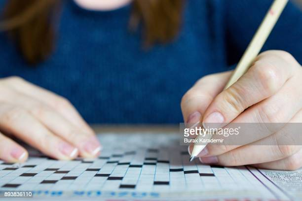 female hand holding a pencil and solves crossword puzzle - single word stock pictures, royalty-free photos & images