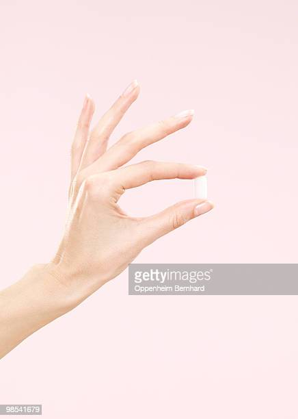 female hand holding a single tablet