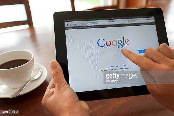 Female hand holding an ipad showing Google.