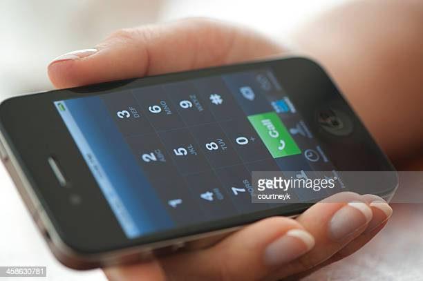Female hand holding an iphone displaying the dialling interface