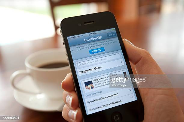 female hand holding an iphone showing twitter - log on stock photos and pictures