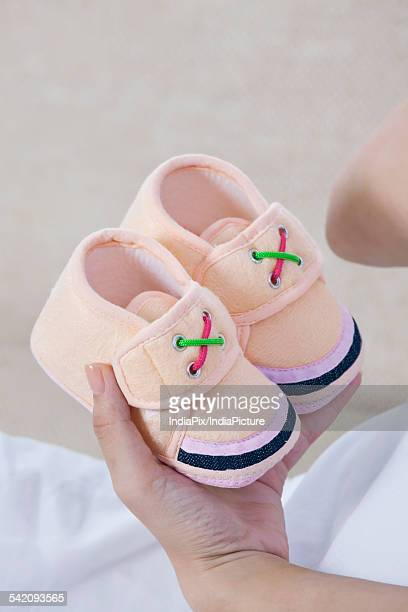 Female hand holding baby booties