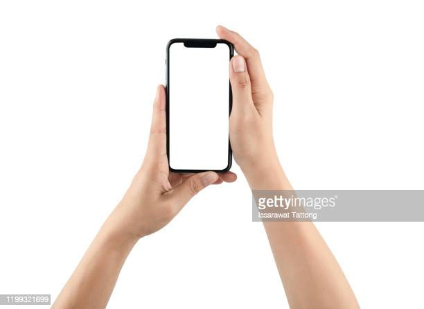 female hand holding black cellphone with white screen at isolated background. - iphone mockup stock pictures, royalty-free photos & images