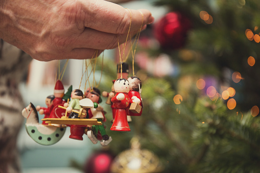 Female hand holding christmas decorations about to put them on tree - gettyimageskorea