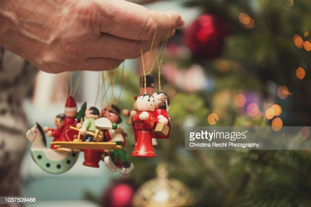 Female hand holding christmas decorations about to put them on tree