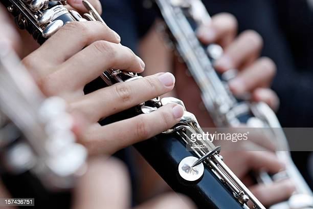 Female hand holding clarinet while playing in orchestra, close-up