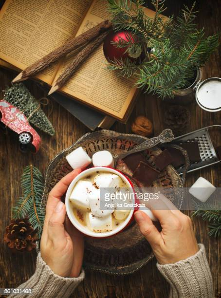 Female hand holding cup of hot chocolate with marshmallow on white table from above