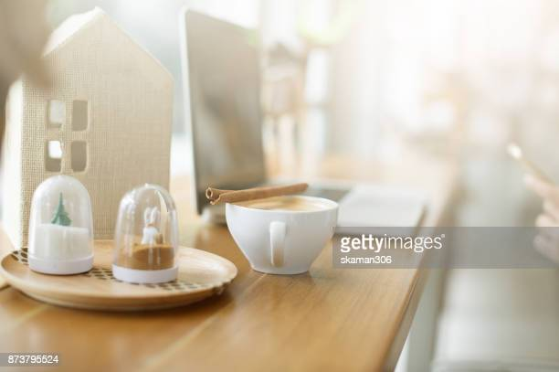 female hand holding japanese green tea (Matcha) on wooden table after working finish