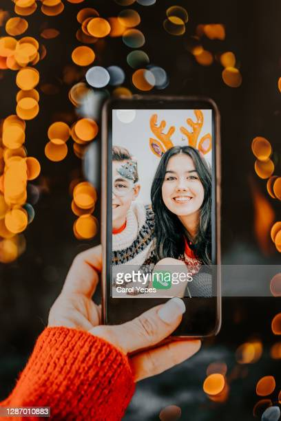 female hand holding mobile device showing video call with kids in christmas time - 12 17 months stock pictures, royalty-free photos & images