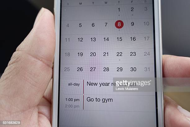Female hand holding mobile phone with new year resolution reminder to go to gym