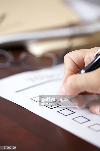 Female hand holding pen about to make a check mark on paper
