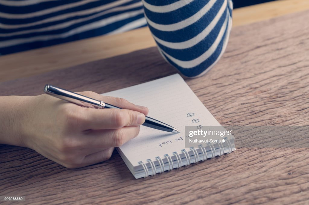 Female hand holding pen writing business plan to do list on wood table in vintage color effect, task priority and work or day to day organize : Stock Photo