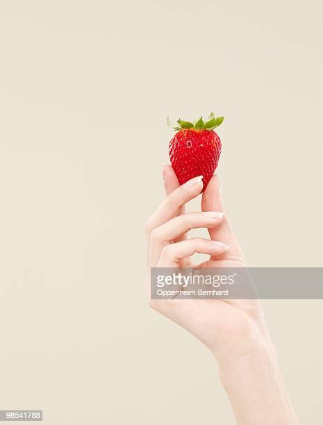 female hand holding single strawberry