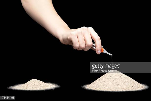 Female hand moving pile of sand with tweezers