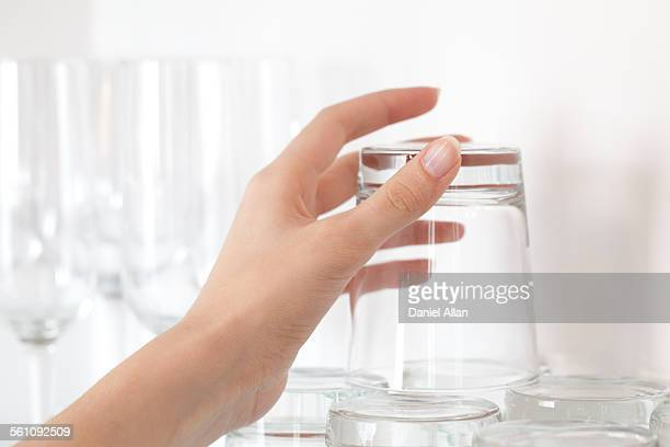 Female hand picking up empty drinking glass