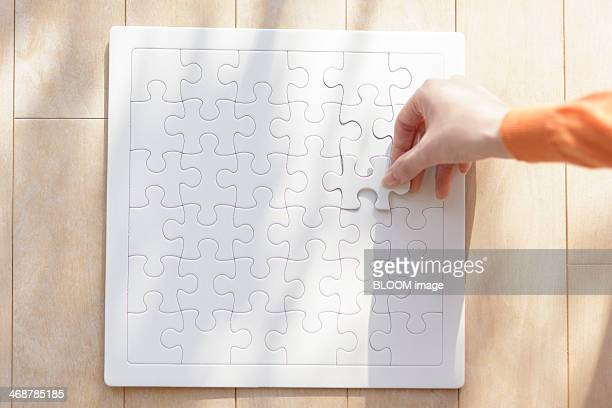 Female hand piecing jigsaw puzzle together