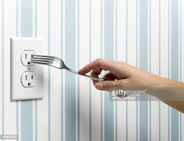 female hand placing fork in outlet - careless stock pictures, royalty-free photos & images