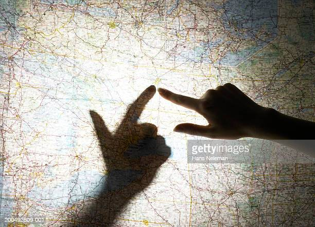 female hand pointing finger at map, casting shadow, close-up - dedo humano imagens e fotografias de stock