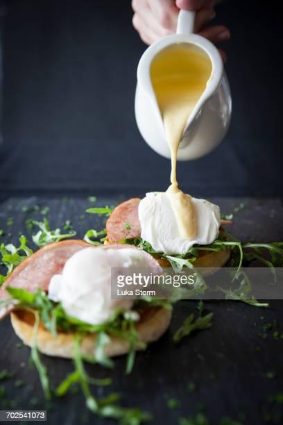 Female hand pouring hollandaise sauce over eggs benedict breakfast on slate
