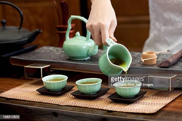 Female hand pouring tea into tea cups