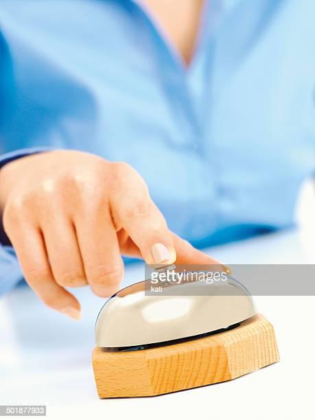 Female hand pressing a porter bell