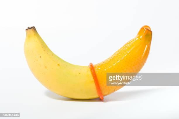 Female hand puts on a condom onto a banana. Safe sex concept.