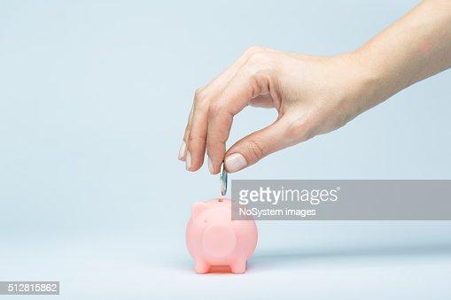 femmina mano mettendo una moneta nel salvadanaio a