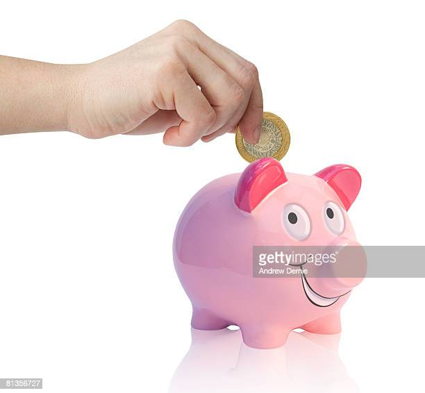 female hand putting money into a pink  piggy bank. isolated on white. - andrew dernie foto e immagini stock