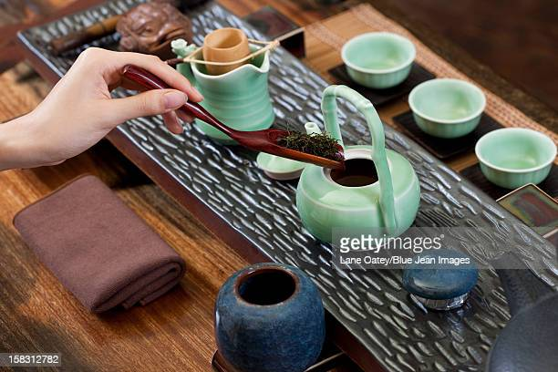 female hand putting tea leaves into teapot - ceremony stock pictures, royalty-free photos & images