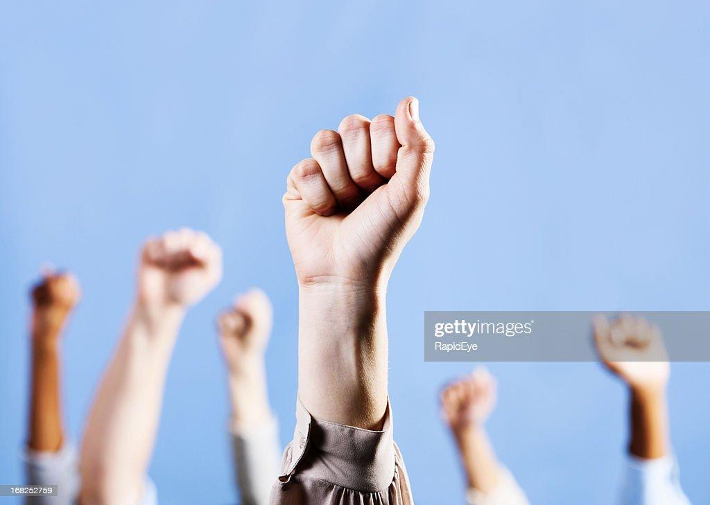 Feminino mão levanta apertadas punho de solidariedade, outros em segundo plano : Foto de stock