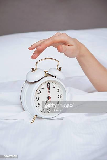 Female hand reaching for alarm clock