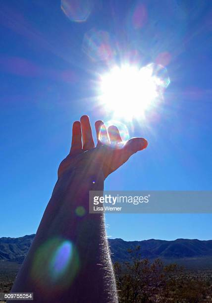 female hand reaching for the sun - spiritual enlightenment stock pictures, royalty-free photos & images