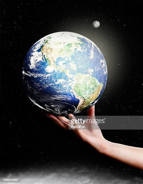 Female hand supports Earth against starfield