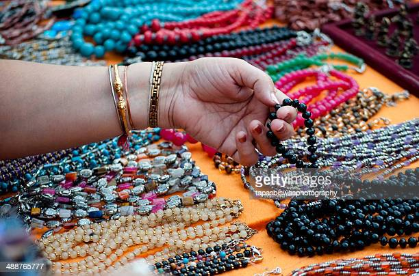 Female hand touching colorful necklaces