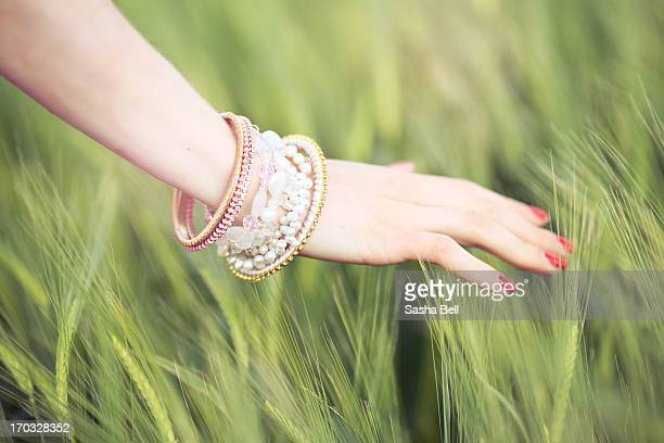 Female hand touching green barley