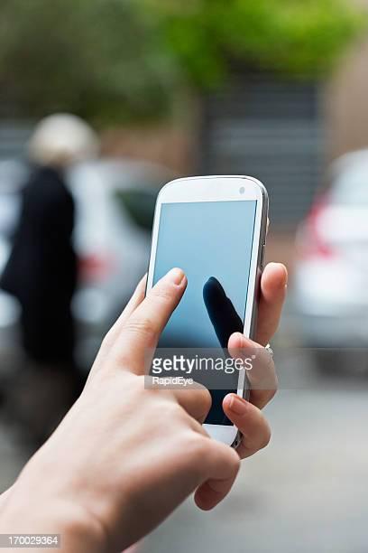 手のスマートフォンを使用して女性の屋外