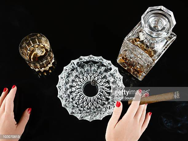 Female hand with cigar whiskey decanter