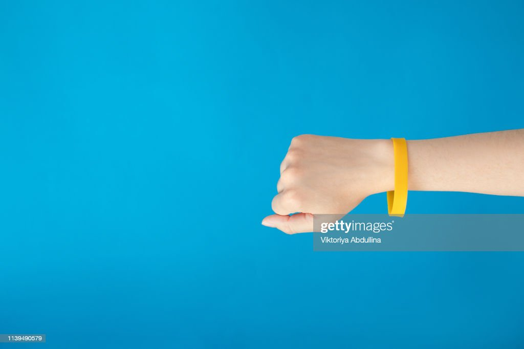 Female hand with empty yellow bracelet on blue background.  Clear sweat band mock up design. : Stock Photo